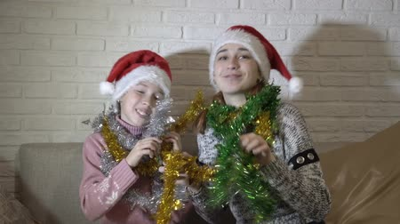 Happy family, two sisters, in Santas hats playing with colorful tinsel, sit and dance on the couch against a white brick wall, look at the camera and smile. Wideo