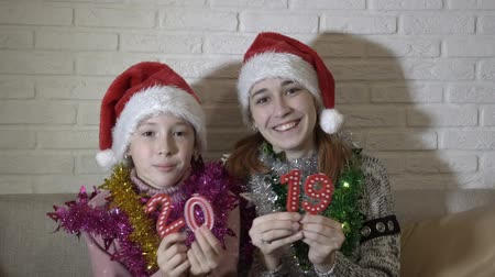 Two happy little girls show the camera figures 2019. They sit and dance in Santas hats on the couch against a white brick wall and smile. Close up.