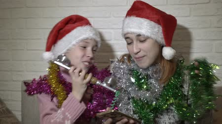 мишура : Happy kids in caps of Santa Claus are singing in the old handset, sit and dance on the couch in front of a white wall with tinsel on his shoulders and smiling.