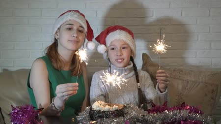 Happy family, two girls, small and a teenager in the hat of Santa Claus with lit sparklers at the cake sitting on the sofa, looking at him and smiling. Christmas.