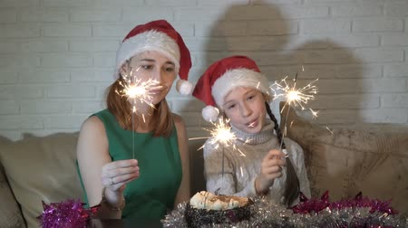 Happy children in Santas hats with lighted sparklers play sitting on the couch near the cake and smile.
