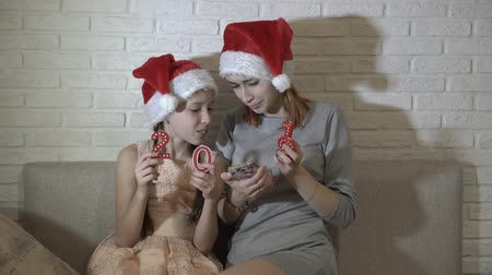 Happy children, two young sisters, sitting in Santas hats, looking at the smartphone, smiling and holding the numbers 2019 in their hands. Portrait. 4K. 25 fps
