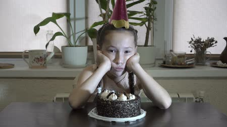 Sad little girl sitting at the table with his head propped up with his hands with a festive cap on his head and looks at the camera. Before her on the table is a cake. Close up. 4K. 25 fps