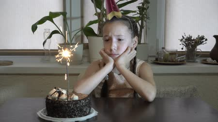 A sad child, a little girl, sits at the table and looks at the burning Sparkler and the cake that is on the table. She sits supporting his head in his hands. Close up. 4K. 25 fps Wideo
