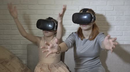 Children play virtual games. Two sisters in virtual reality glasses sit and play at home on the couch against a white brick wall. They wave their hands and look around. Close up. 4K. 25 fps