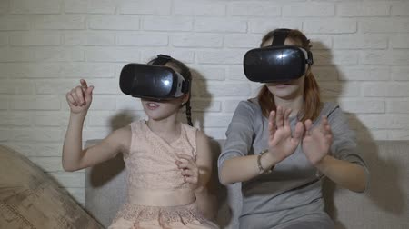Two young girls in black virtual reality glasses sit and play virtual games. They wave their hands, press virtual buttons and explore the surrounding space. Close up. 4K. 25 fps