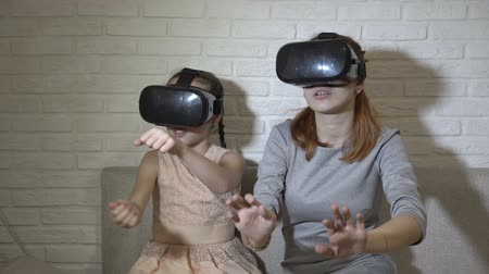 A little girl and her teenage sister in virtual reality glasses sitting and playing virtual games at home on the couch on a white background. They wave their hands and look around.