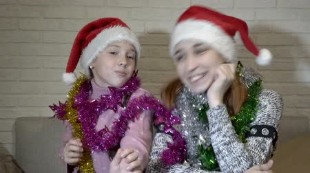 Portrait of two happy cheerful children who sit in Santas hats with Christmas tinsel on their shoulders. They dance, laugh, move to the music and look at the camera. Close up. 4K. 25 fps