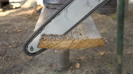 power equipment : A man saws off a piece of an old Board with an electric saw, resting his foot on it. Close up. Side view. 4K. 25 fps.