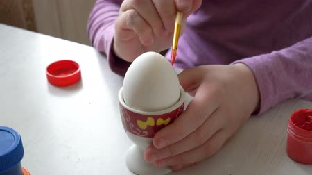 Close-up, white Easter egg stands on a stand, and the child draws on it with a brush. 4K. 25 fps