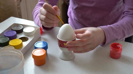 A little girl draws with a brush and colored paints on a white egg, sitting at home at the table. Close up. 4K. 25 fps