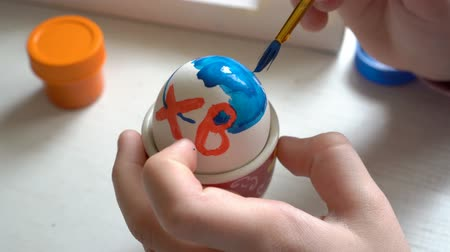 Close-up, the child paints a white Easter egg with a brush and blue paint. The view from the top. 4K. 25 fps Filmati Stock