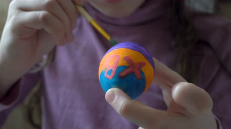 A little girl holds an Easter egg in her hand and paints on it a brush and colored paints, sitting at home at the table. Close up. 4K. 25 fps