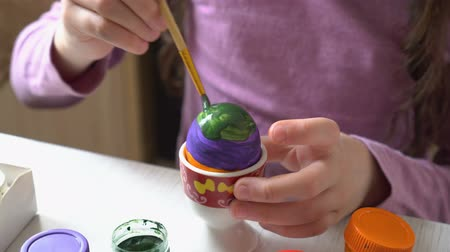 A little girl paints an Easter egg with colorful colors sitting at home at the table. Close up. 4K. 25 fps