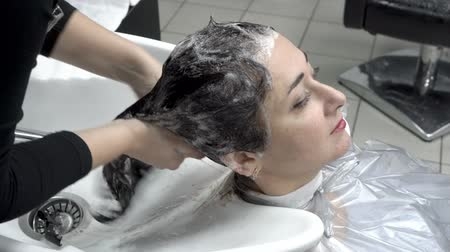 Hairdresser washes the head of a beautiful Oriental girl in the beauty salon after the hair coloring procedure. Hair care. Close up. 4K. 25 fps