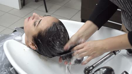 Hair care. The hairdresser washes the girls head after the haircut in the Barber shop over a white washbasin shampoo. Close up. 4K. 25 fps Wideo
