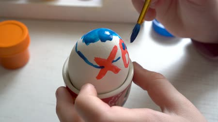 Extremely close-up, the child paints the Easter egg blue and red paint, sitting at the table. 4K. 25 fps