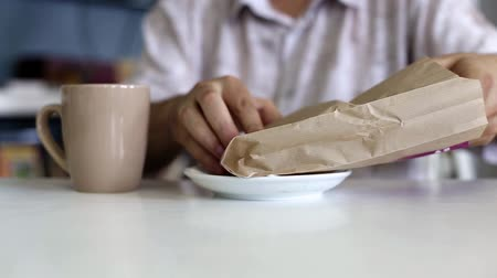 Man unpacks a sandwich while sitting in a cafe