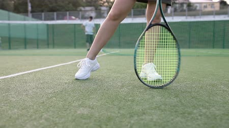 teniszütő : The camera moves around the girl on the tennis court In the background a guy bounces the ball with a squeeze racket Stock mozgókép