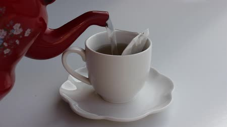 teabag : Womans hand putting down a tea cup and pouring hot water in it. Stock Footage
