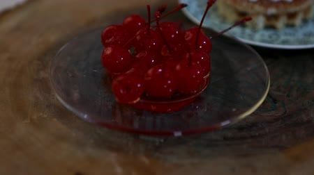 засахаренный : Candied cherry with sprigs in a glass plate, approaching and moving away from the camera.