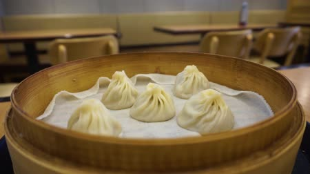 bamboo steamer : Five Chinese Steamed Xiaolongbao Dumplings in a Bamboo Steamer Stock Footage