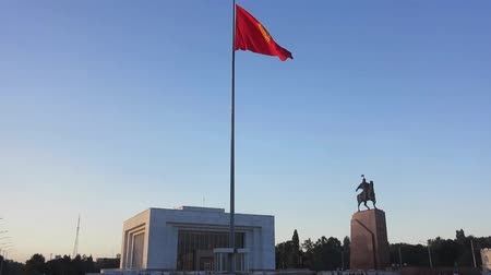 heroes square : Kyrgyzstan Waving Flag on Flagpole with Hero Manas Monument
