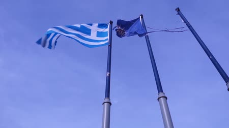 nationality : Greek and Blue Colored Macedonian Vergina Sun Flag Waving on Flagpoles Stock Footage