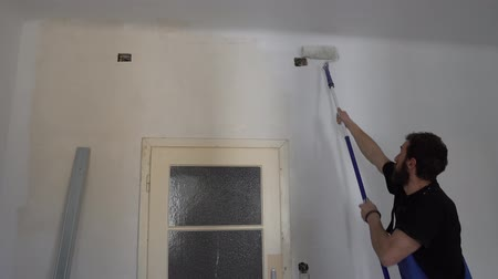 wristband : Young Caucasian Brown Haired Man with Beard and Black T-Shirt Blue Dungarees Working Trousers Painting with Paint Stick Roller Pole and Fresh White Paint the Wall from Top to Bottom