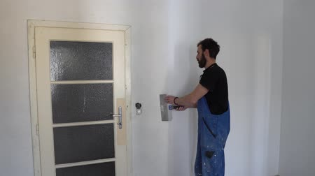 wristband : Young Caucasian Brown Haired Man with Beard and Black T-Shirt Blue Dungarees Working Trousers Removed excess White Paint Crust from Wall with Long Skimming Refina Facade Spatula Stock Footage