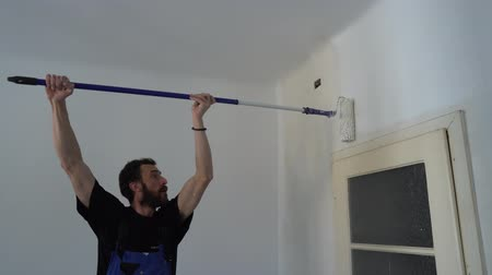 wet t shirt : Young Caucasian Brown Haired Man with Beard and Black T-Shirt Blue Dungarees Working Trousers is Painting with Paint Stick Roller Pole and Fresh White Paint the Wall from Left to Right Stock Footage