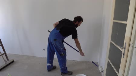 wristband : Young Caucasian Brown Haired Man with Beard and Black T-shirt Blue Dungarees Working Trousers Painting with Paint Stick Roller Pole and Fresh White Paint the Wall from Bottom to Top