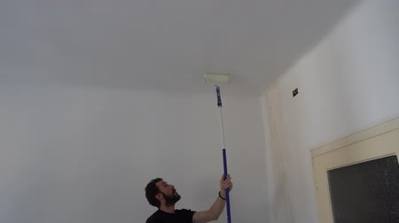 браслет : Young Caucasian Brown Haired Man with Beard and Black T-Shirt Blue Dungarees Working Trousers is Painting with Paint Stick Roller Extension Pole and Fresh White Paint the Ceiling from Left to Right Стоковые видеозаписи