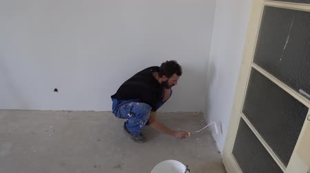 wristband : Young Caucasian Brown Haired Man with Beard and Black T-Shirt Blue Dungarees Working Trousers is Painting with Mini Fabric Roller and Fresh White Paint the Bottom Wall from Left to Right Horizontal Stock Footage