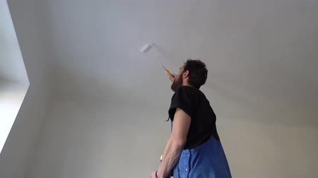 vertically : Dungarees Working Trousers is Standing on Ladder Painting with Mini Fabric Roller and Fresh White Paint the Ceiling Stock Footage