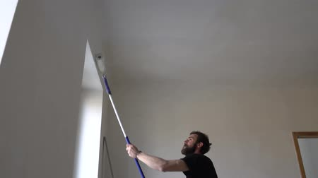 wet t shirt : Young Caucasian Brown Haired Man with Beard and Black T-Shirt Blue Dungarees Working Trousers is Painting with Paint Stick Roller Extension Pole and Fresh White Paint the Ceiling from Left to Right Stock Footage