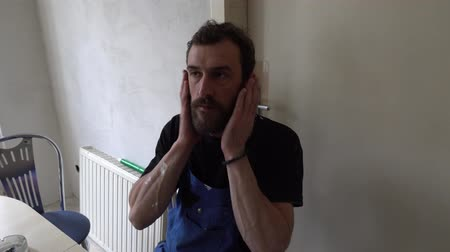 kaloryfer : Young Muscular Worker Caucasian Brown Haired Man with Beard and Black T-Shirt Blue Dungarees Working Trousers is Sitting on a Chair and Straightens Hair with Hands