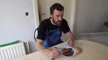 dungarees : Young Muscular Worker Caucasian Brown Haired Man with Beard and Black T-Shirt Blue Dungarees Trousers is Sitting on a Chair Having a Conversation While Eating His Dark Sauce Roast Beef with Cutlery Stock Footage