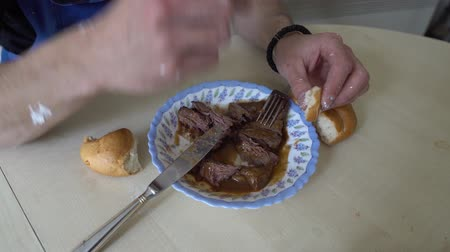 gulasz : Young Caucasian Muscular Worker With Black T-shirt Blue Dungarees Trousers Sitting On A Chair With His Hands Dipping A White Roll In Dark Sauce Roast Beef On A Plate And Cutlery