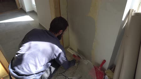 шпатель : Young Caucasian Brown Haired Beard Man in Dark Purple Pullover and Track Pants is Distributing the Spackle Compound on the Wall with a Putty Knife Spatula over the Plaster Mesh Reinforcement