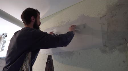 шпатель : Young Caucasian Brown Haired Beard Man in Dark Purple Sweater is Putting the Plaster Mesh Reinforcement Over the Spackle Compound on the Wall and Slightly Pressing it with His Finger