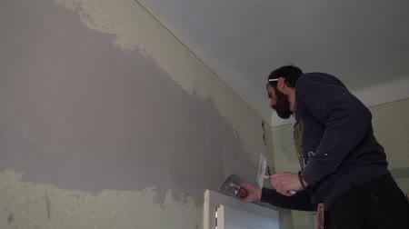 шпатель : Young Caucasian Brown Haired Beard Man in Purple Sweater with a Cigarette on his Ear is Distributing the Spackle Compound on the Wall above the Door with a Putty Knife Spatula from the Bottom Up