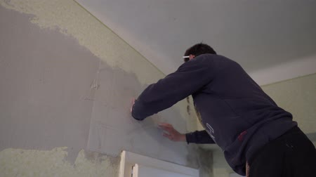 шпатель : Young Caucasian Brown Haired Beard Man in Dark Purple Pullover is Putting the Plaster Mesh Reinforcement over the Spackle Compound on the Wall above the Door and Slightly Pressing it with his Hands
