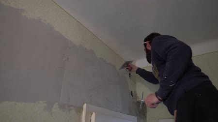 шпатель : Young Caucasian Brown Haired Beard Man in Purple Sweater with a Cigarette on His Ear is Distributing the Spackle Compound over the Plaster Mesh Reinforcement with Putty Knife Spatula from Bottom Up