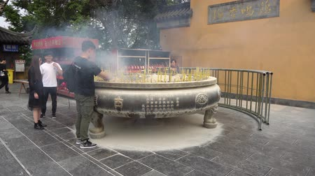 şanslı : At Nanjing Gujiming Buddhist Temple Young People Are Lighting Yellow Colored Incense Candles And Placing Them In A Huge Jar