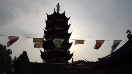 rouge : Nanjing Gujiming Buddhist Temple Pagoda with Waving Colorful Prayer Flags Depicting the Dharmachakra Wheel of Dharma at Late Afternoon Stock Footage