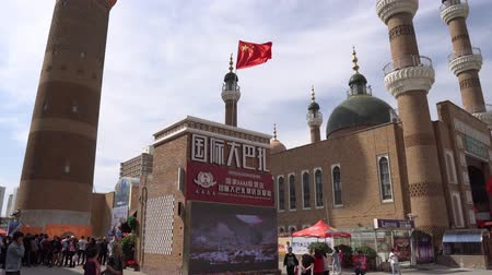 food court : Waving China Flag at Urumqi Grand Bazaar with Chinese Tourists and Green Colored Cupola Mosque at the Background