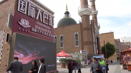 grand mosque : Waving Chinese Flag at Urumqi Grand Bazaar with Chinese Tourists and Green Colored Cupola Mosque at the Background Stock Footage