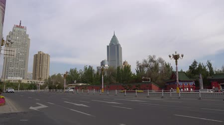 посетитель : In Urumqi Cars are Driving and People Walk in Front of the Peoples Park Entrance with View of Skyscrapers at Background