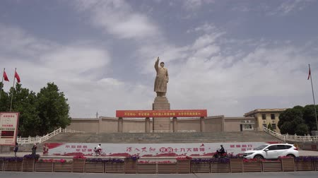 gongyuan : Kashgar Giant Statue of Chairman Mao Zedong at Peoples Park Square with Driving Cars Bicycles Walking People and Waving Chinese Flags Stock Footage
